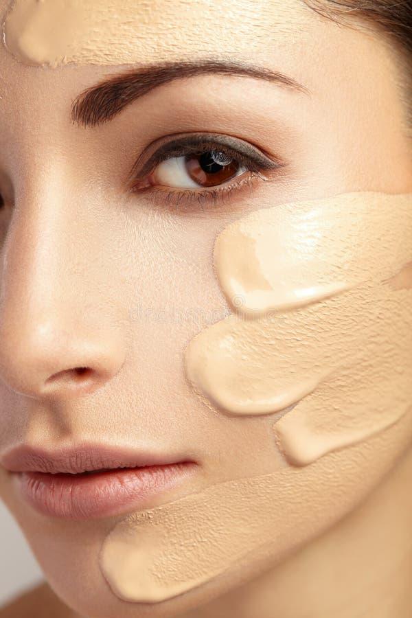 Mujer joven con la fundación cosmética en una piel foto de archivo