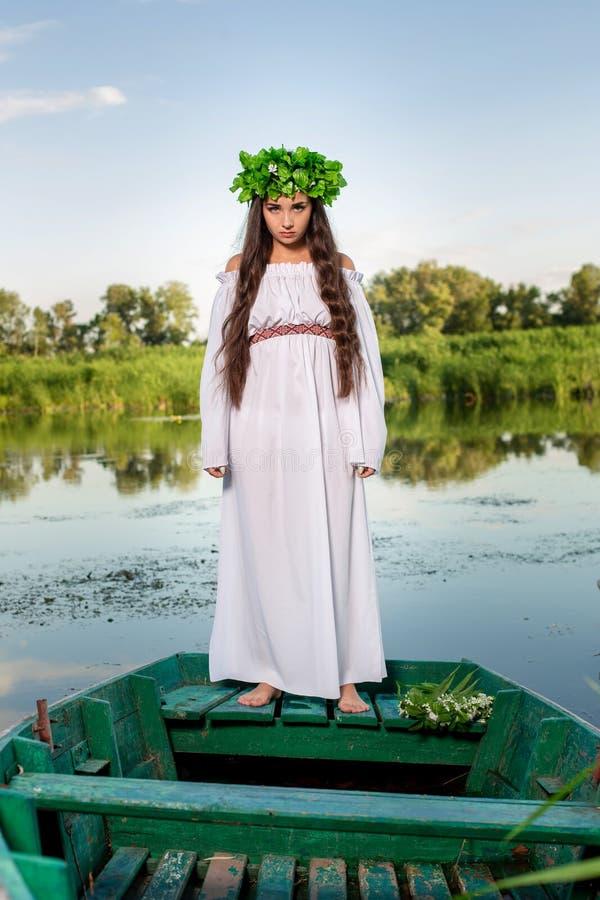 Mujer joven con la guirnalda de la flor en su cabeza, relajándose en el barco en el río en la puesta del sol Concepto de la belle imagenes de archivo