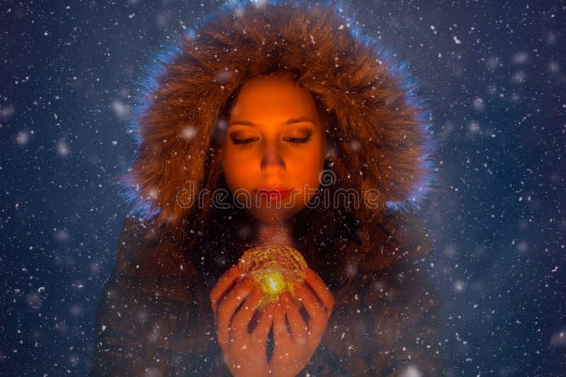 Mujer joven con la luz mágica en manos en la noche durante una nevada imagenes de archivo