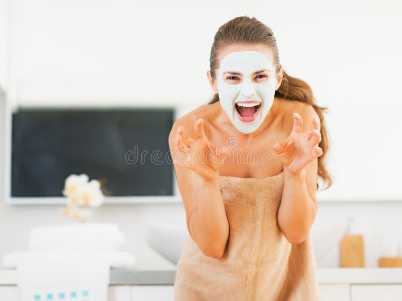 Mujer joven con la máscara cosmética en asustar de la cara fotos de archivo
