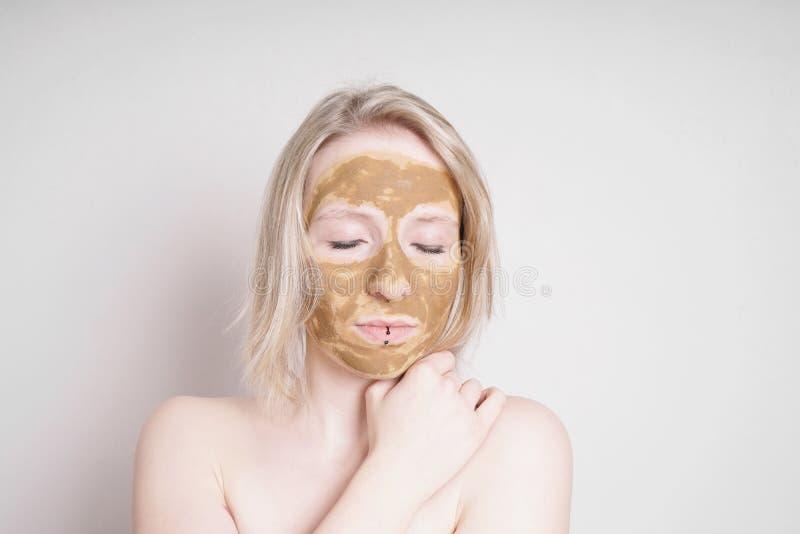 Mujer joven con la máscara facial de la belleza de la tierra o de la arcilla de la cura que disfruta del tratamiento de la salud foto de archivo