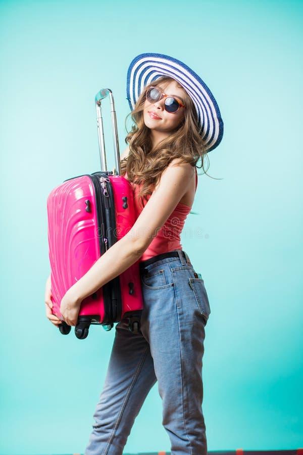 Mujer joven con la maleta aislada en fondo azul imagenes de archivo