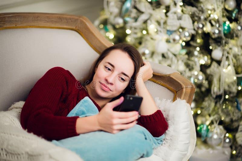 Mujer joven con la mentira casera del teléfono móvil en un sofá delante del árbol de abeto foto de archivo libre de regalías