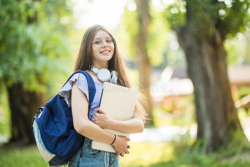 Mujer joven con la mochila que camina a través de parque verde con el ordenador portátil de plata en manos fotografía de archivo libre de regalías
