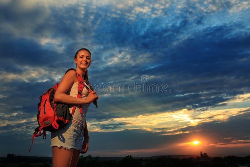 Mujer joven con la mochila roja que camina el verano de la puesta del sol imagen de archivo libre de regalías