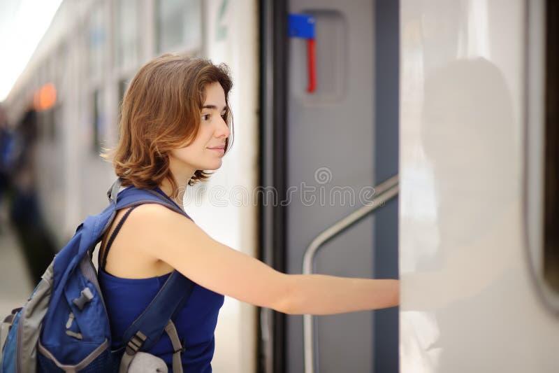 Mujer joven con la mochila tomar el tren imágenes de archivo libres de regalías