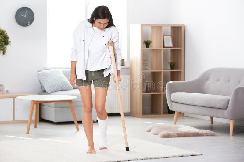 Mujer joven con la muleta y la pierna quebrada en molde foto de archivo libre de regalías