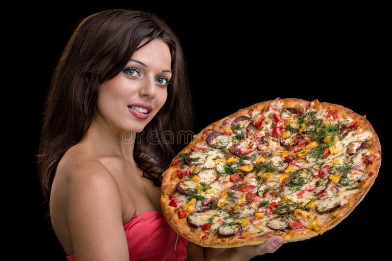 Mujer joven con la pizza contra fondo negro fotos de archivo
