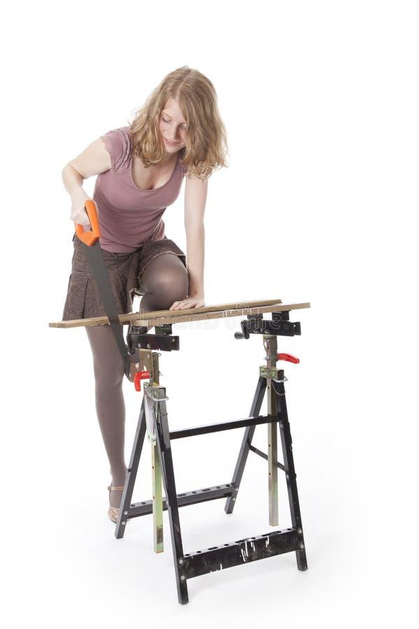 Mujer joven con la sierra de madera imagen de archivo libre de regalías