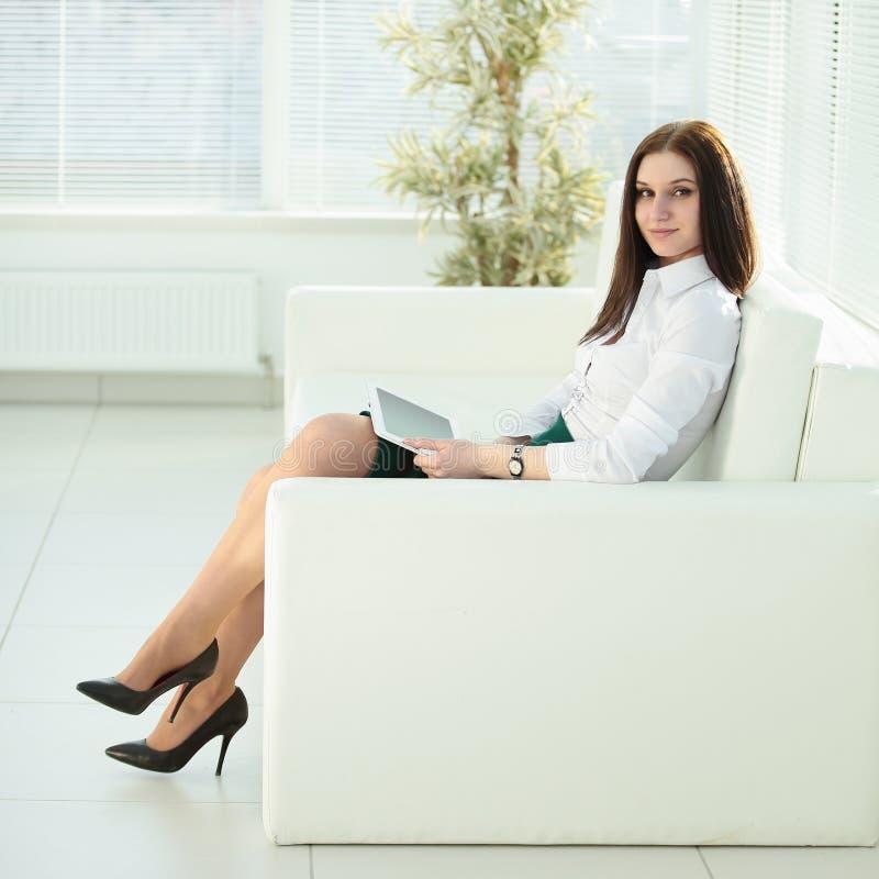Mujer joven con la tableta digital que se sienta en el pasillo de la oficina fotografía de archivo libre de regalías