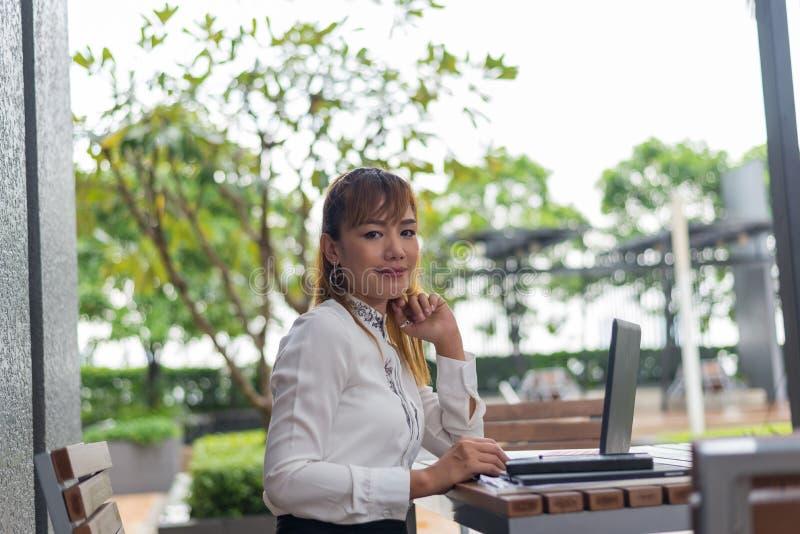 Mujer joven con la tableta hacia fuera en la ciudad foto de archivo