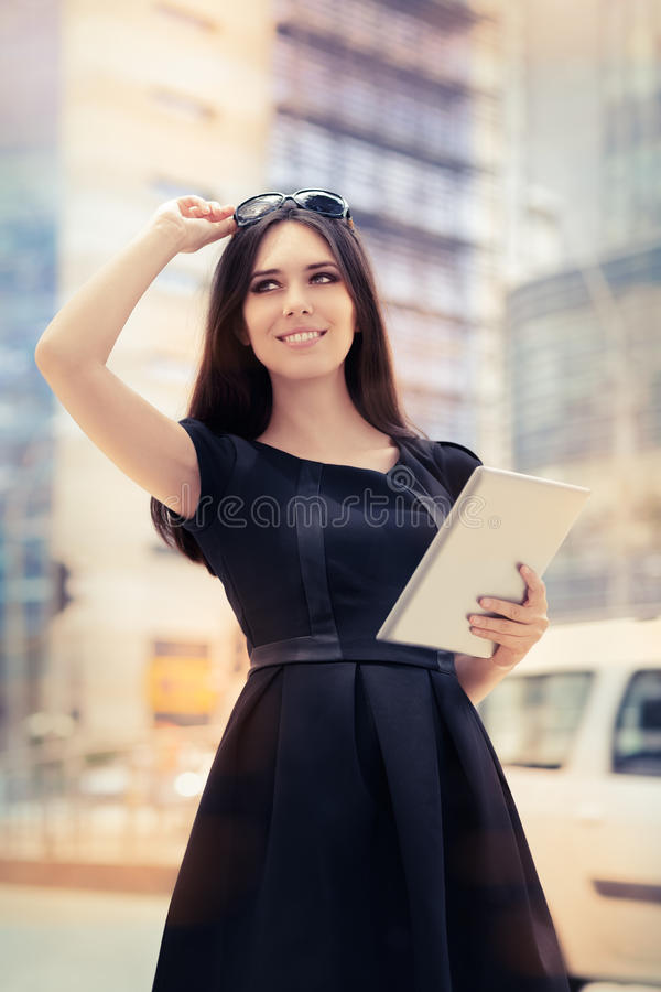 Mujer joven con la tableta hacia fuera en la ciudad fotos de archivo