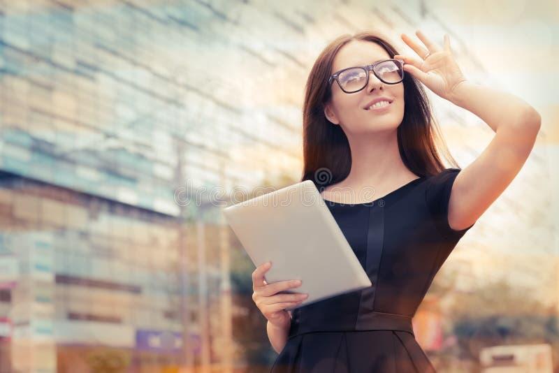 Mujer joven con la tableta hacia fuera en la ciudad imagen de archivo