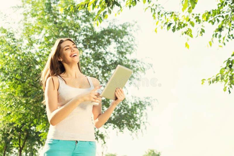 Mujer joven con la tableta y el café en la risa del parque imagen de archivo libre de regalías