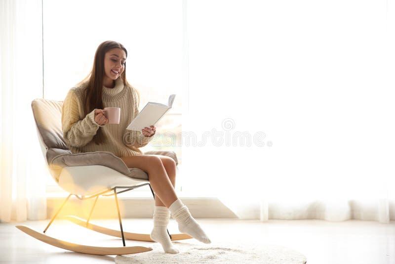 Mujer joven con la taza de libro de lectura del café cerca de la ventana en casa fotos de archivo