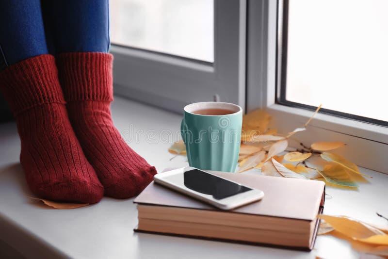 Mujer joven con la taza de té, de teléfono móvil y de hojas de otoño sentándose en alféizar en casa fotografía de archivo