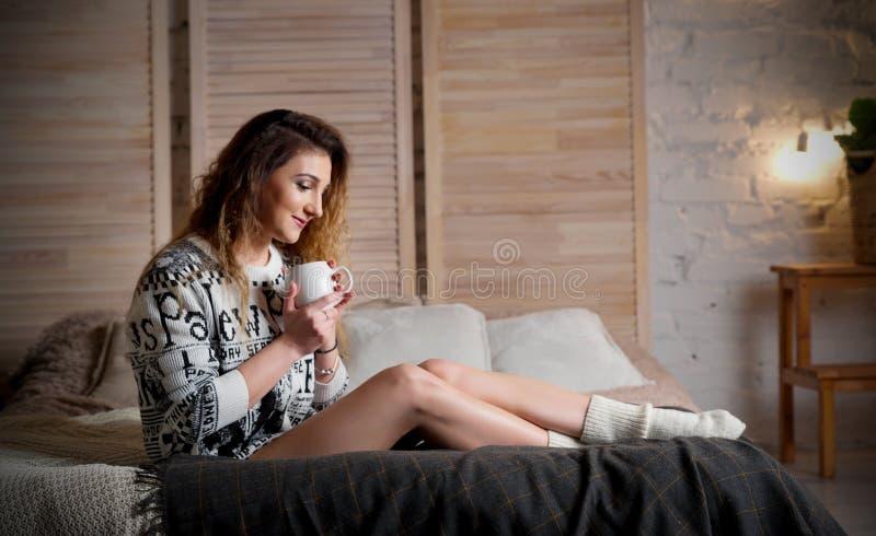 Mujer joven con la taza en cama fotos de archivo