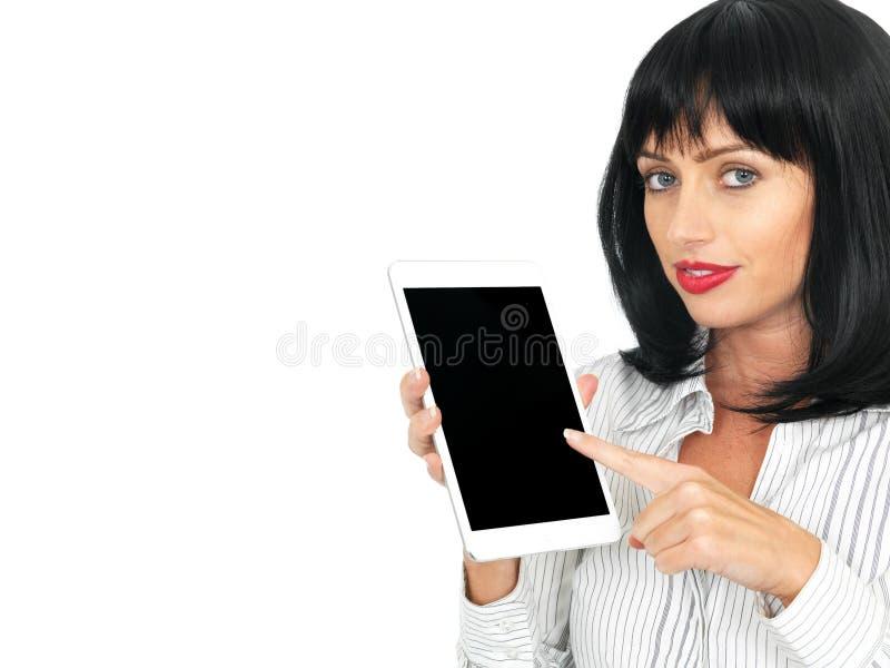 Mujer joven con la tenencia y usar de la oscuridad una tableta del ordenador foto de archivo libre de regalías