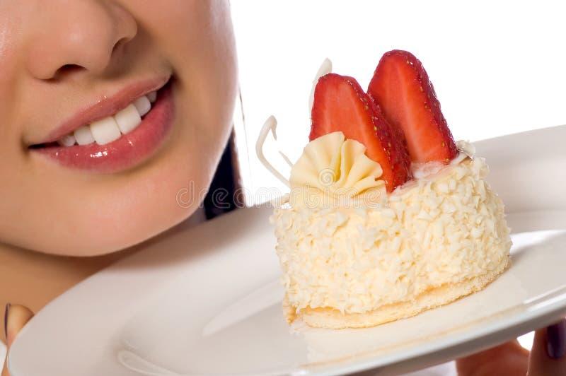 Mujer joven con la torta de las fresas imagen de archivo