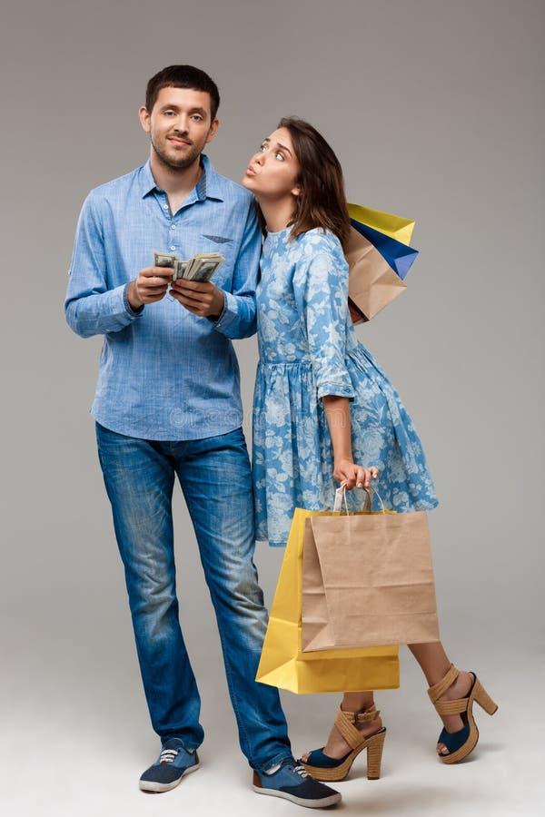 Mujer joven con las compras, hombre que sostiene el dinero sobre fondo gris imagen de archivo