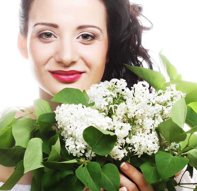 Mujer joven con las flores blancas sobre el fondo blanco imágenes de archivo libres de regalías