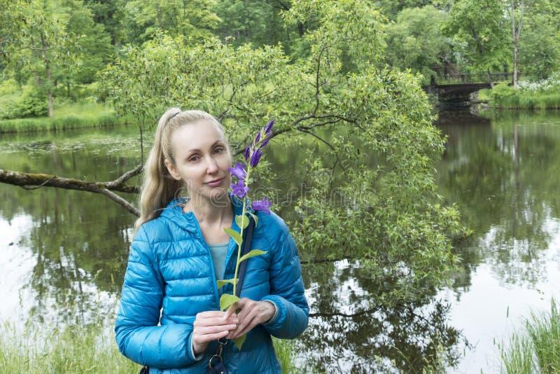 Mujer joven con las flores de campana salvajes por el lago foto de archivo