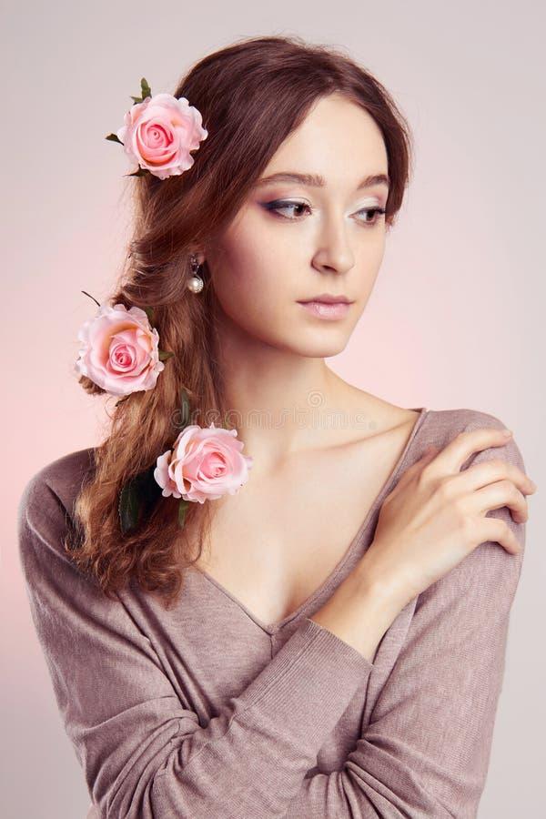 Mujer joven con las flores en pelos fotografía de archivo