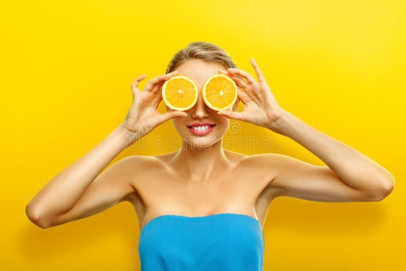 Mujer joven con las frutas en fondo anaranjado brillante fotografía de archivo