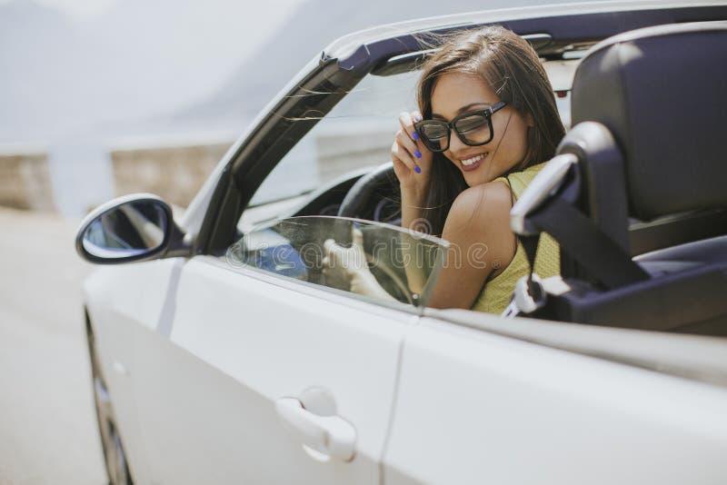 Mujer joven con las gafas de sol que conducen su autom?vil superior convertible en d?a soleado brillante fotografía de archivo