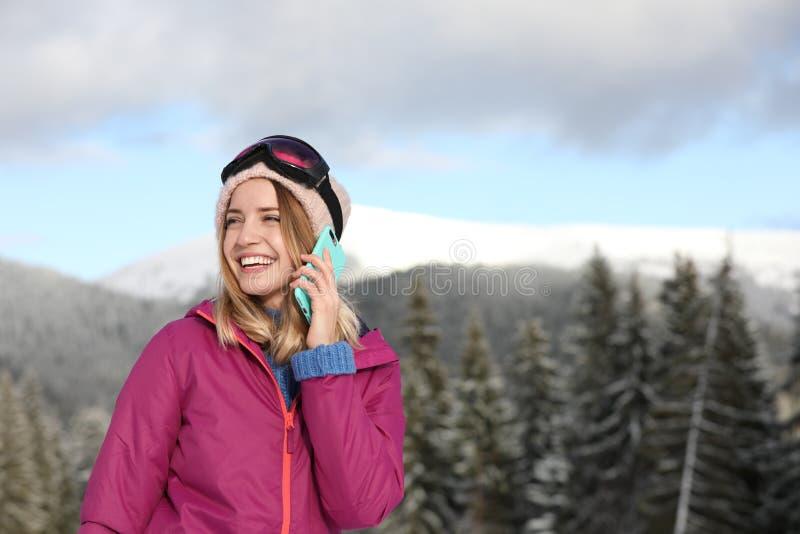 Mujer joven con las gafas del esquí que habla en el teléfono en montañas durante vacaciones del invierno imagenes de archivo