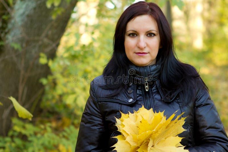 Mujer joven con las hojas de otoño amarillas foto de archivo