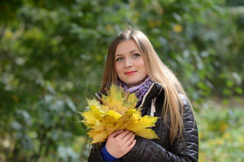 Mujer joven con las hojas de otoño a disposición imágenes de archivo libres de regalías