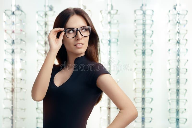 Mujer joven con las lentes en tienda óptica fotografía de archivo libre de regalías