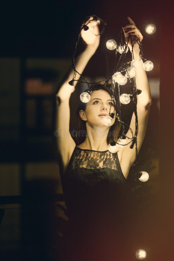 Mujer joven con las luces de hadas imagen de archivo
