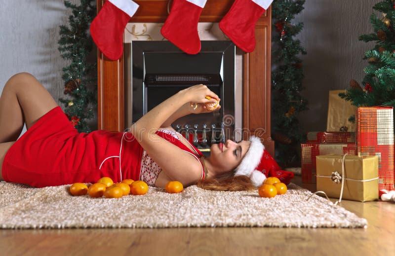 Mujer joven con las mandarinas en el cuarto con decoratio de la Navidad foto de archivo
