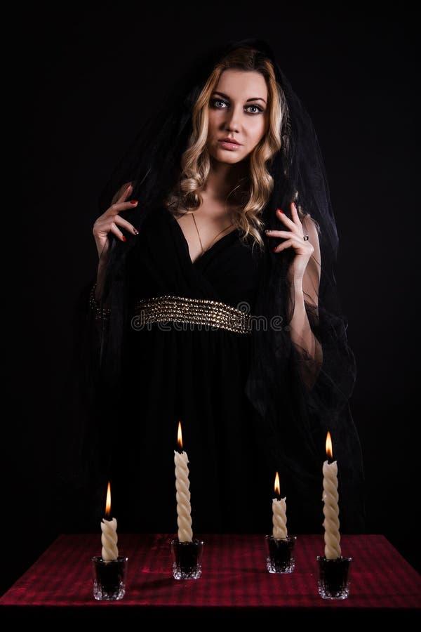 Mujer joven con las velas en oscuridad foto de archivo