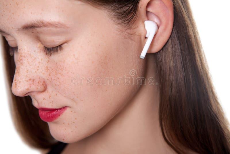 Mujer joven con los auriculares inalámbricos fotografía de archivo libre de regalías