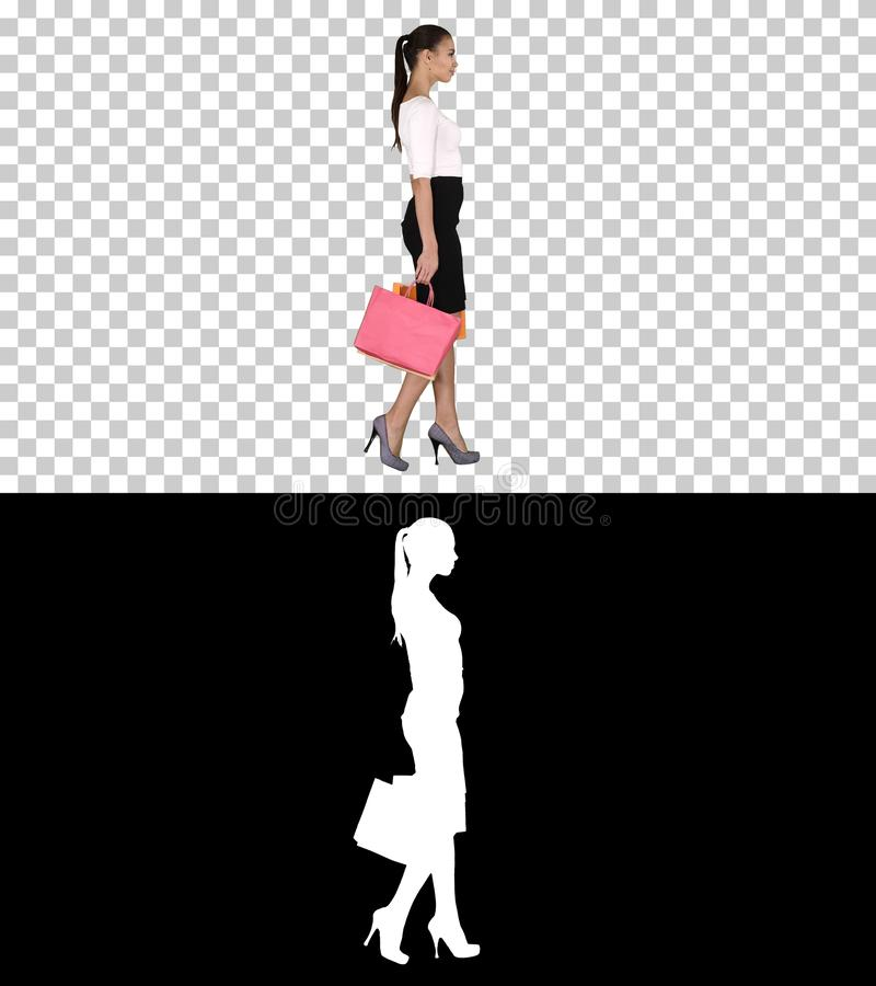 Mujer joven con los bolsos de compras que sale de la tienda, Alpha Channel foto de archivo libre de regalías