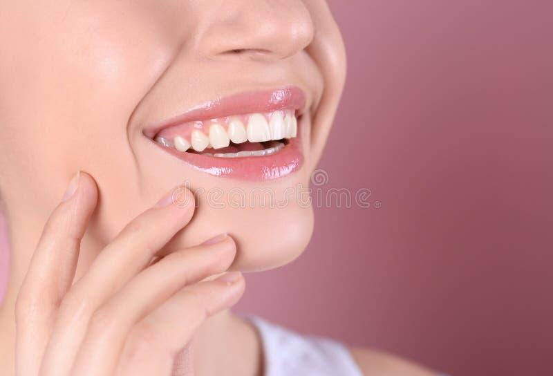 Mujer joven con los dientes sanos y sonrisa hermosa en el fondo del color, primer fotos de archivo libres de regalías