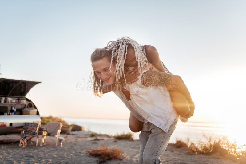 Mujer joven con los dreadlocks que abrazan a su hombre hermoso fuerte firmemente fotografía de archivo libre de regalías