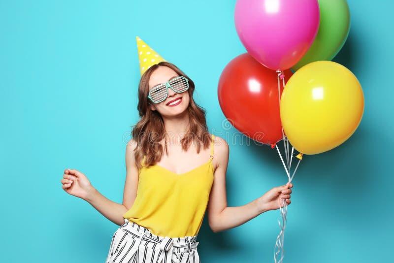 Mujer joven con los globos en fondo del color Celebración del cumpleaños imagen de archivo libre de regalías