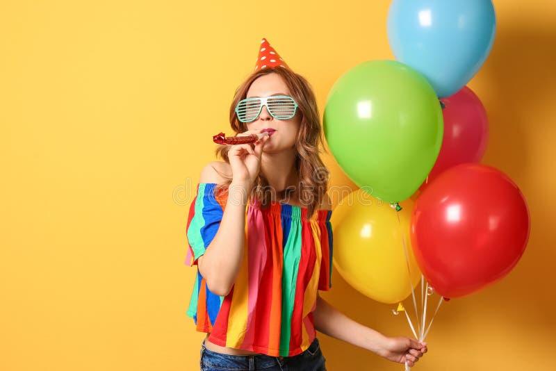 Mujer joven con los globos y ventilador del partido en fondo del color Celebración del cumpleaños fotos de archivo