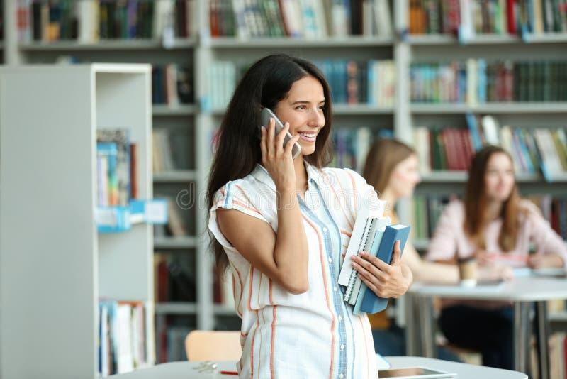 Mujer joven con los libros que habla en el teléfono fotografía de archivo libre de regalías
