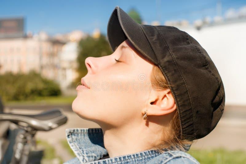 Mujer joven con los ojos cerrados contra paisaje urbano del verano fotografía de archivo