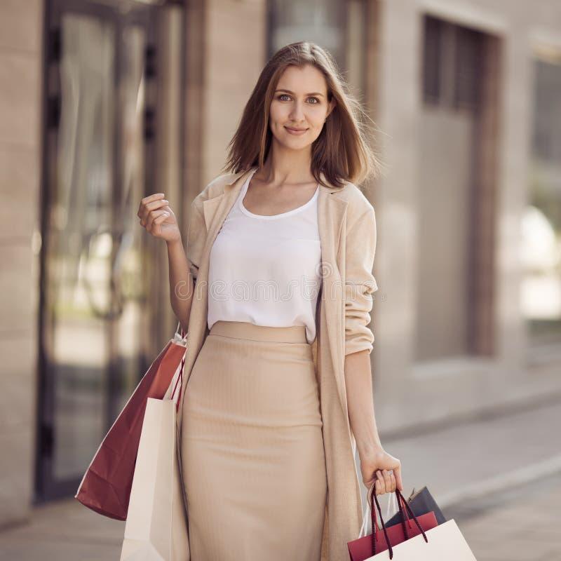 Mujer joven con los panieres que camina en la calle imagen de archivo libre de regalías