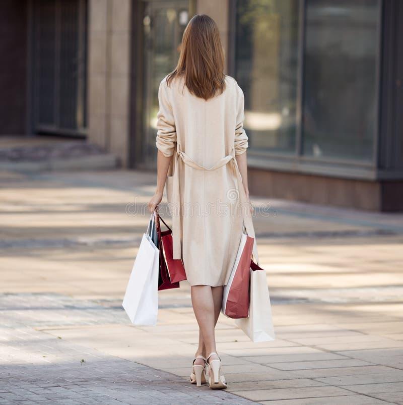 Mujer joven con los panieres que camina en la calle imagenes de archivo