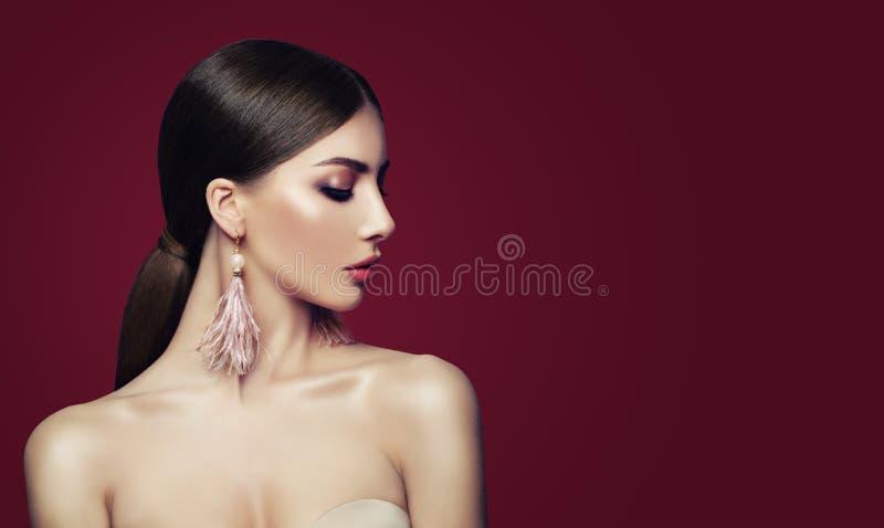 Mujer joven con los pendientes de la joyería de la moda imagen de archivo