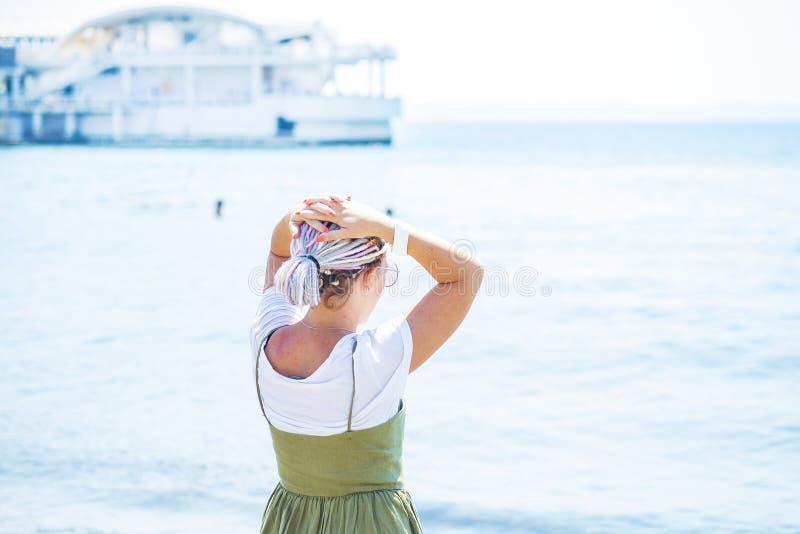 Mujer joven con los soportes multicolores de los dreadlocks en la playa foto de archivo libre de regalías