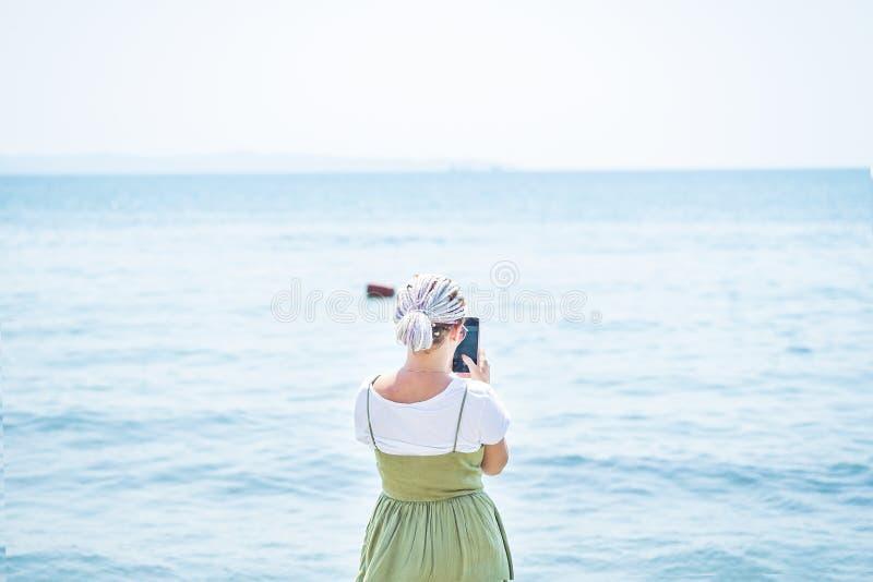 Mujer joven con los soportes multicolores de los dreadlocks en la playa imágenes de archivo libres de regalías