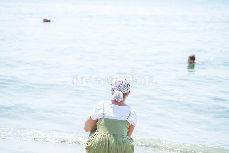 Mujer joven con los soportes multicolores de los dreadlocks en la playa imagen de archivo